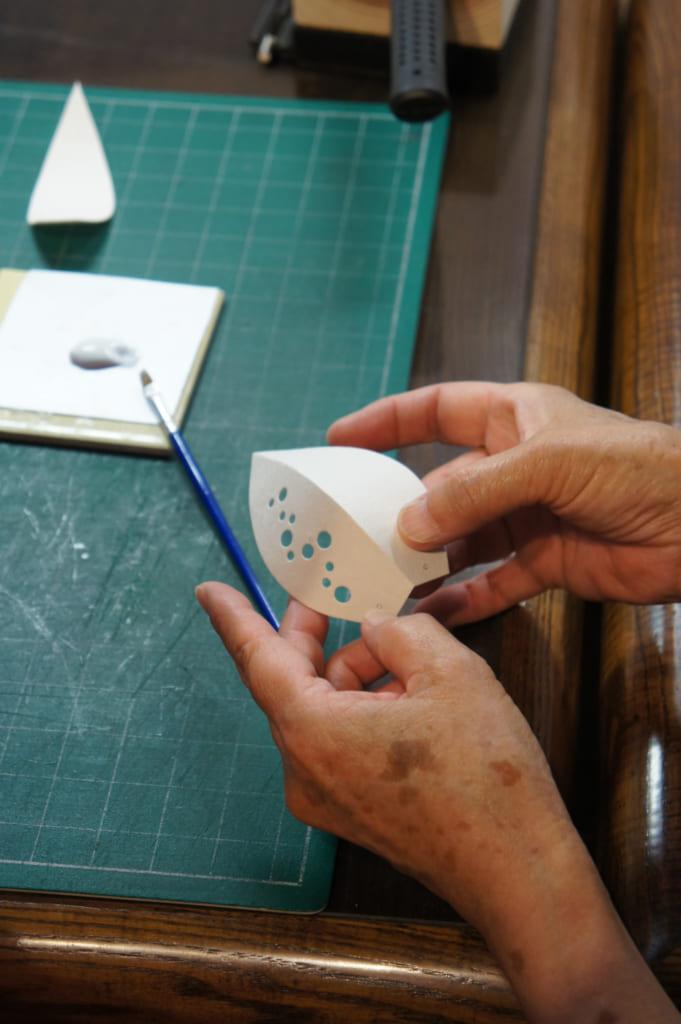 Gros plan sur les mains de l'artisane montant comment assembler les parties de la lampe