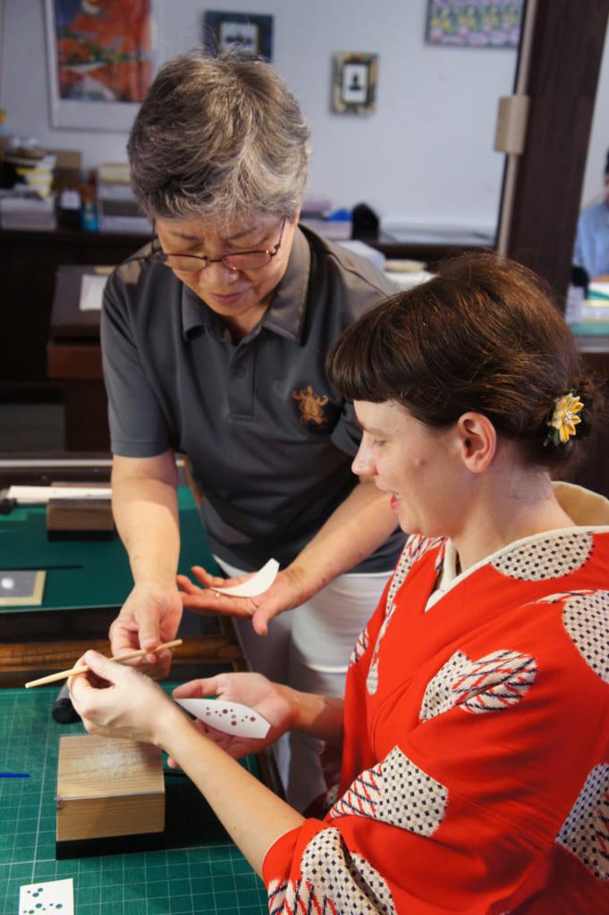 Une artisane donnant des instructions à Clémentine pendant l'atelier