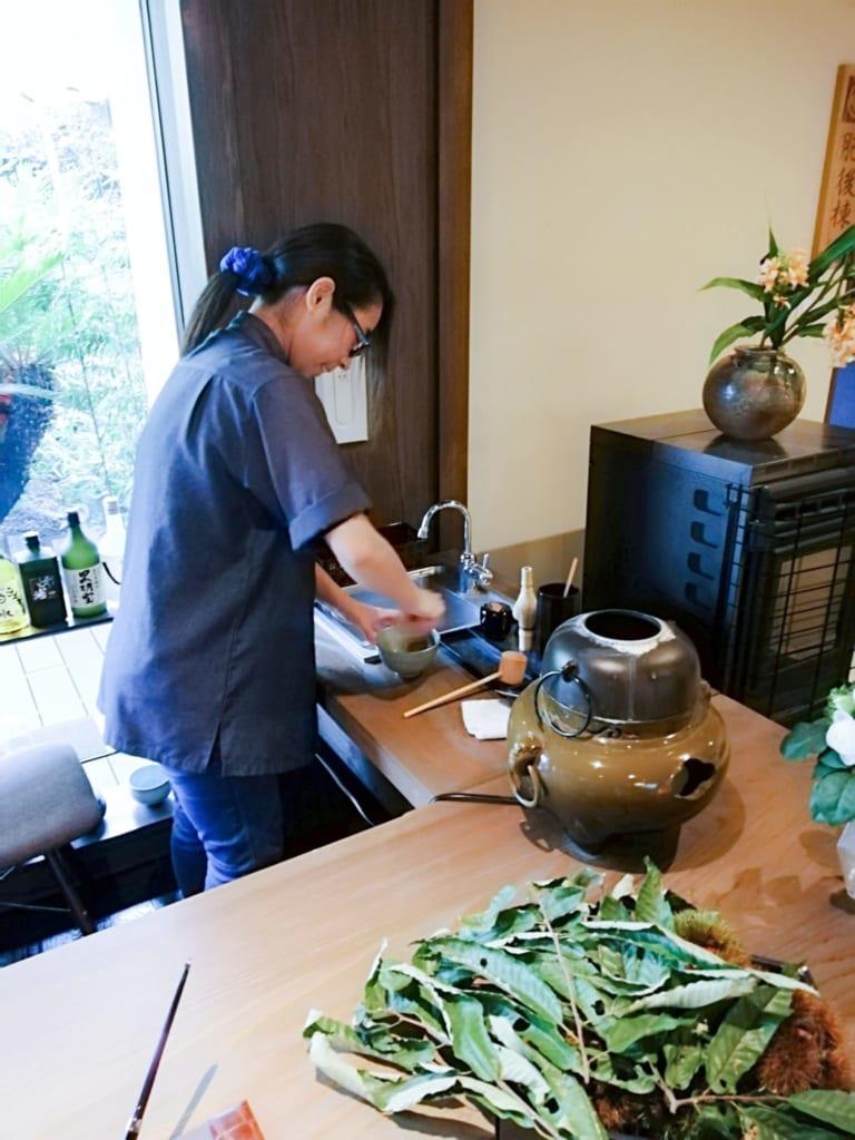 Personnel préparant du thé à l'accueil du ryokan Kafutei