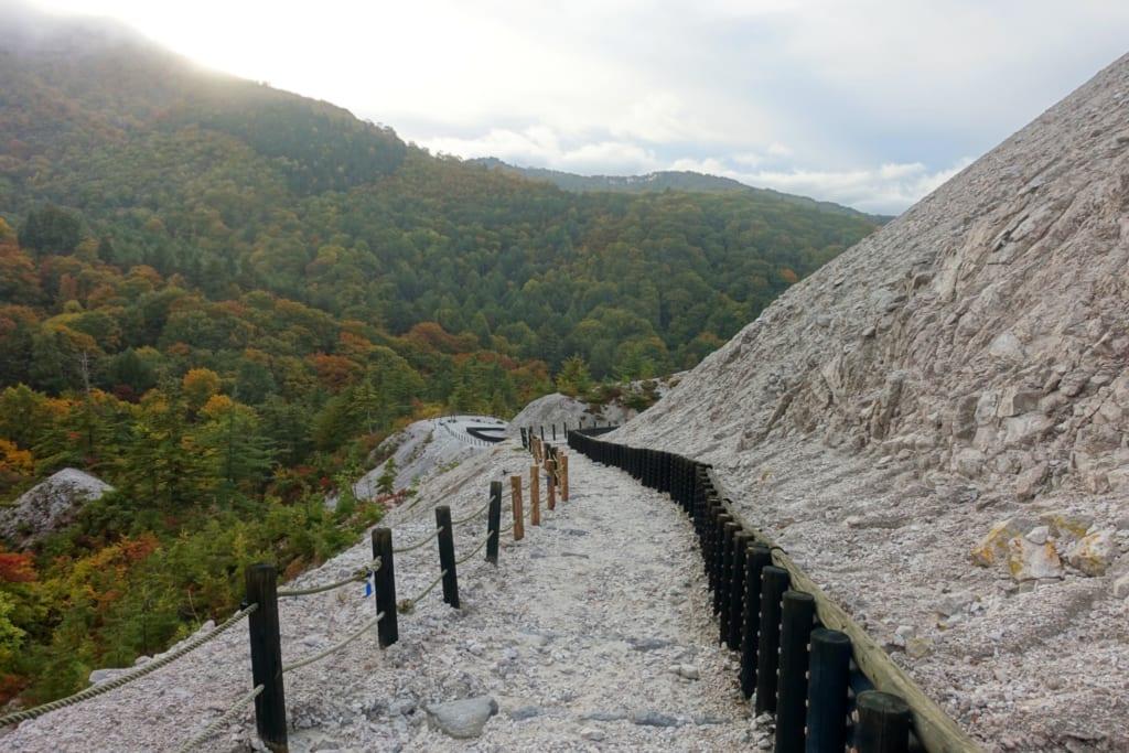 Un chemin de pierres blanches du kawarage jigoku s'étend vers l'horizon au milieu des montagnes verdoyantes de la préfecture d'Akita