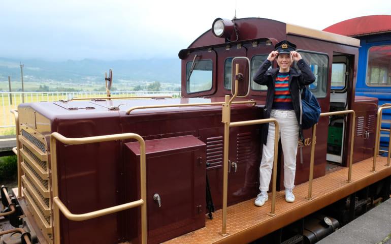 Je pose devant la locomotive du train torokko, coiffée de la casquette du conducteur de train