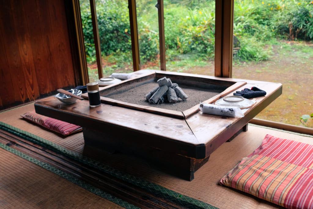 Foyer et charbon au centre d'une table de Takamori Dengaku Hozonkai donnant sur le jardin