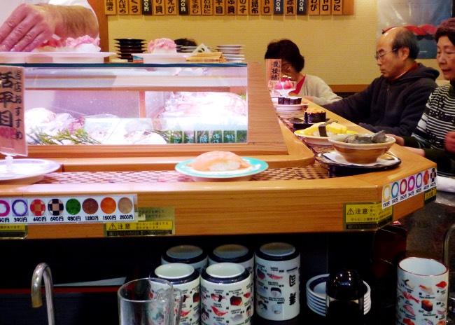 Interno di un ristorante kaiten-zushi, con nastro trasportatore e clienti seduti al bancone