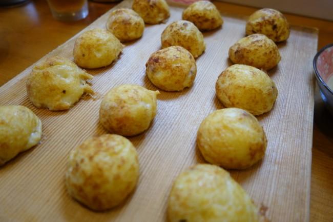 akashiyaki takoyaki dumplings on a wooden cutting board (まな板)