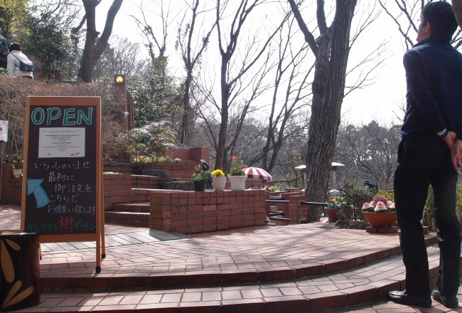Man props his back over sturdy brick spread, cafe Itsuki Garden terrace off Daibutsu hiking course, Kamakura