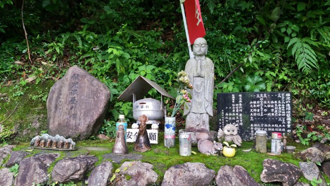 Offerings of items near a statue.