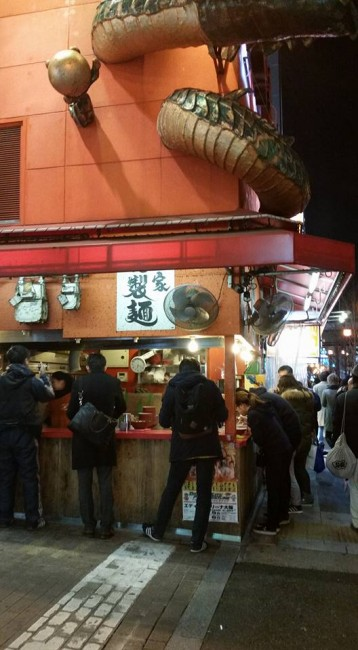 Standing, eating at a streetside Tachigui ramen noodles stand restaurant, Osaka