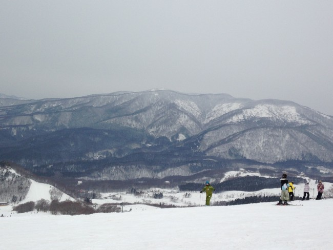People skiing atop the snow with mountains in the distance.