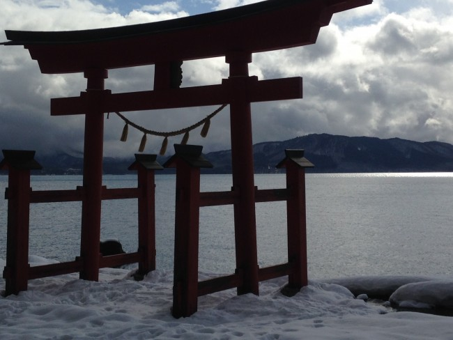 Close up of the Tori gate at the snow and beach before the water.