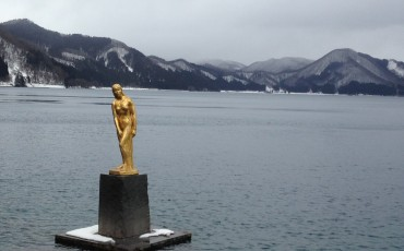 Golden statue on top of the lake that's great for sightseeing near the beach with some snow..