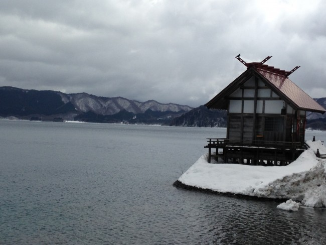 Side shot from the beach of the small building surrounded by snow and water.