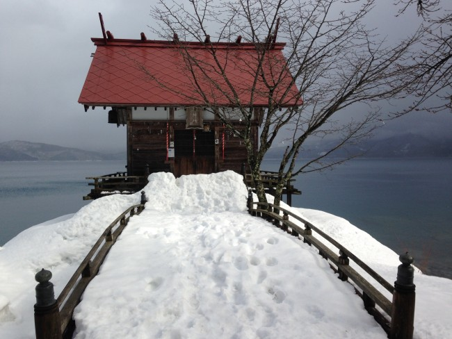 Little building surrounded by water that has a snowy bridge path from the beach.