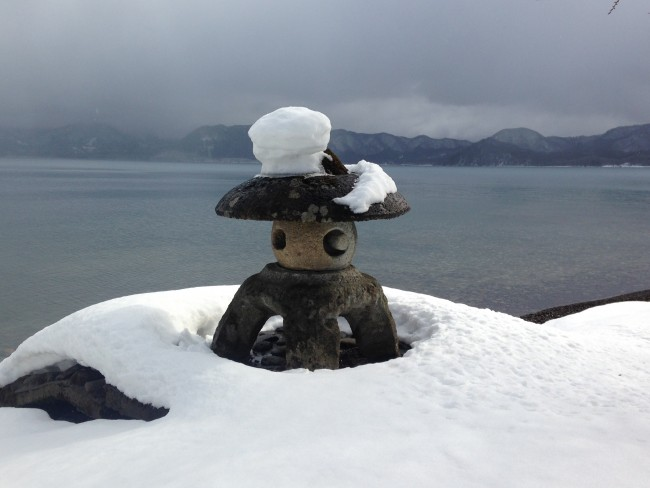 Stone statue surrounded by snow near the beach and water.