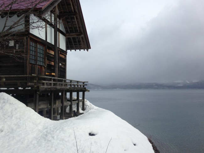 Cabin that is near the beach that has snow and the water nearby.