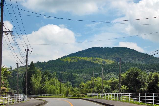 Street and mountain full of trees on the way to Kirishima Jingu Shrine.