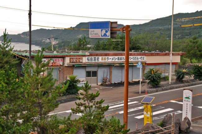 A road and buildings being with some nature on the island of Sakurajima.