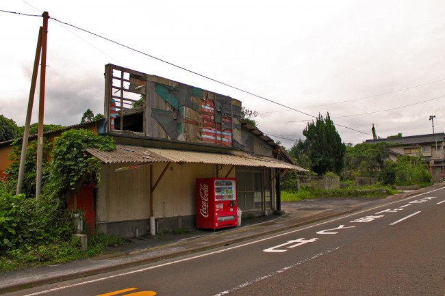 A road and abandoned building being slowly consumed by nature on the island of Sakurajima.