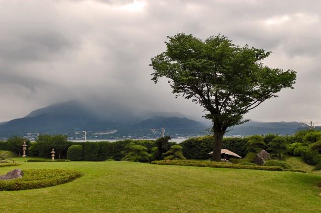 View of Sakurajima from grassy Sengan-en garden.
