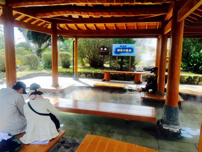 People resting around benches near a foot onsen at Beppu.