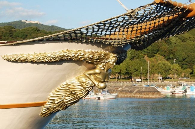 gold figurine on the bowspirit of a sightseeing cruise ship
