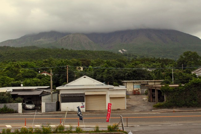 Clouds covering the volcano and surrounding nature at the island of Sakurajima with a house and road at the front..