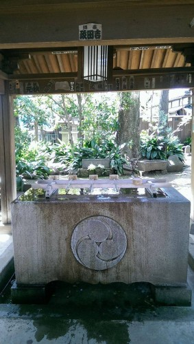 Cleansing station at Okusawa shrine gate in Tokyo.