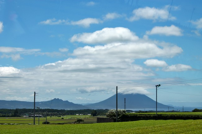Green nature scenery of Kagoshima with the mountain and clouds in the background.