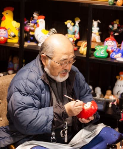Der Handwerker bemalt Daruma, Fukushima, Tohuko, Japan.