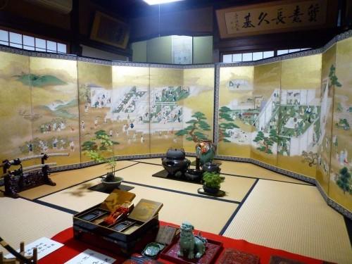 Kokonoe-en's folding screen collection on display, with bonsai.