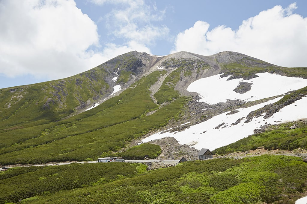 Some snow remaining on the top of a green mountain in Nagano