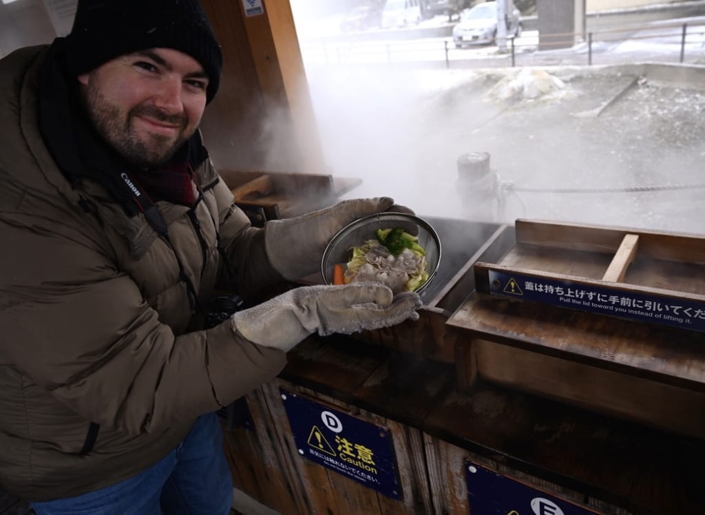 Mark putting his lunch in the natural steamer in Shikabe