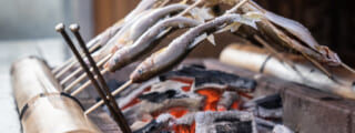 Skewered fish grilling over charcoal
